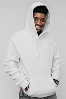 Junger afroamerikanermann, der einen weißen kapuzenpulli trägt