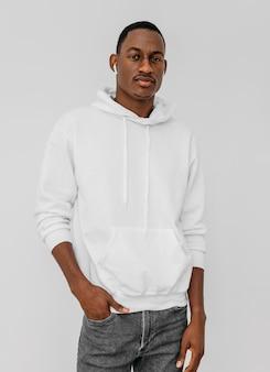 Junger afroamerikanermann, der einen weißen kapuzenpulli und ein paar ohrhörer trägt