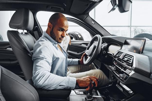 Junger afroamerikanermann, der in einem neuen auto sitzt