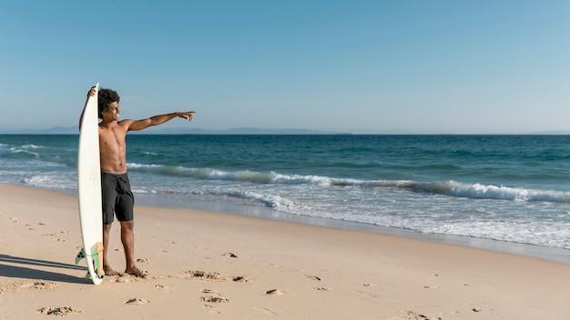 Junger afroamerikanermann, der in ozean zeigt