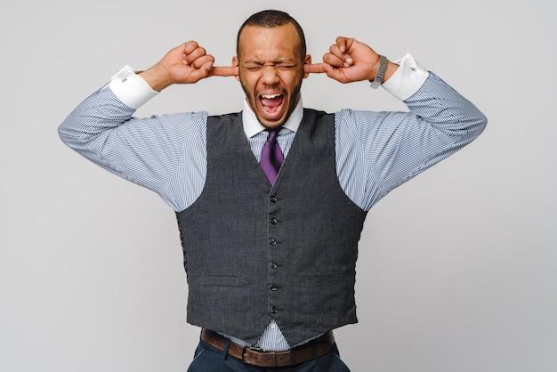 Junger afroamerikanermann, der seine hände zu seinen ohren hält und schreit