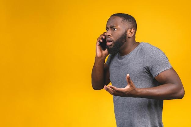 Junger afroamerikanermann, der smartphone verwendet, gestresst, schockiert mit scham und überraschungsgesicht, wütend und frustriert. angst und aufregung wegen irrtums.