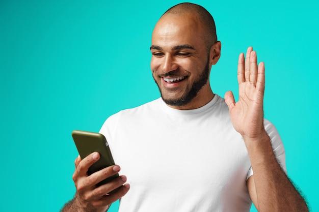 Junger afroamerikanermann, der videoanruf mit seinem smartphone macht
