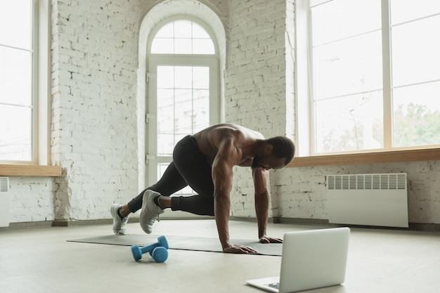 Junger afroamerikanermann, der zu hause trainiert und fitnessübungen, aerobic macht.