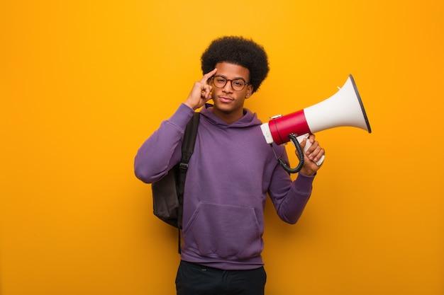 Junger afroamerikanermann holdinga ein megaphon, das an eine idee denkt