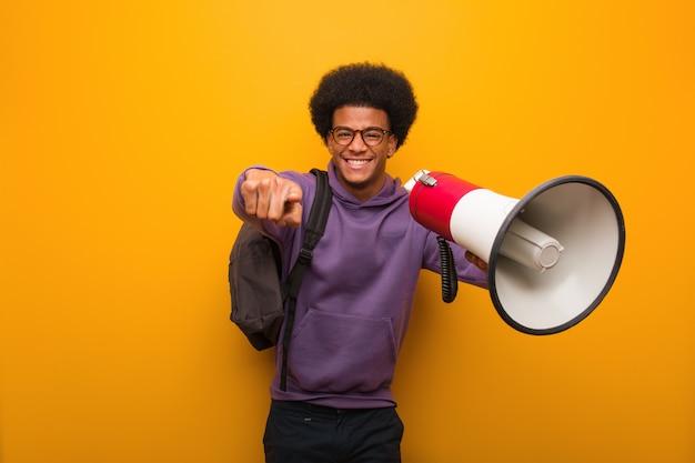 Junger afroamerikanermann holdinga ein megaphon nett und lächelnd, zeigend auf front