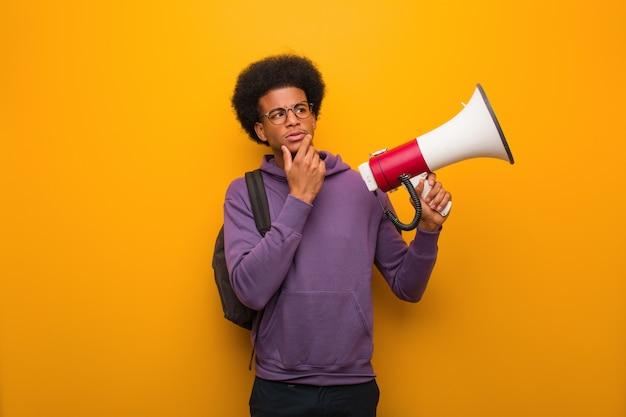Junger afroamerikanermann holdinga ein zweifelndes und verwirrtes megaphon