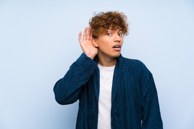 Junger afroamerikanermann in den pyjamas etwas hörend