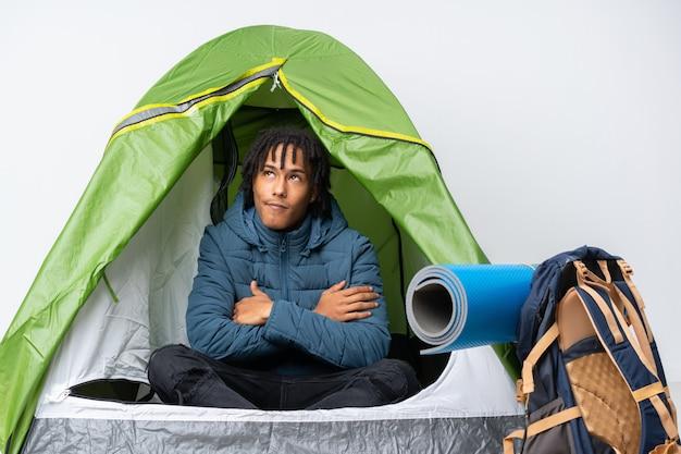 Junger afroamerikanermann in einem grünen zelt des campings, das beim lächeln nach oben schaut