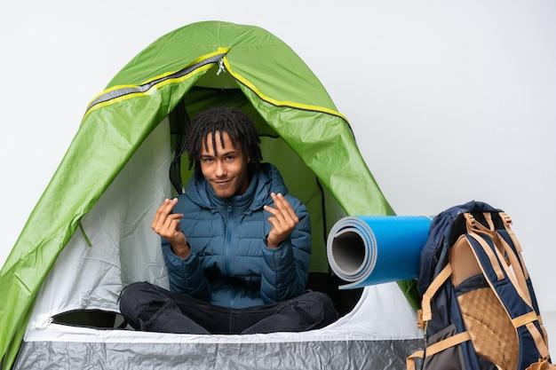 Junger afroamerikanermann in einem grünen zelt des campings, das geldgeste macht