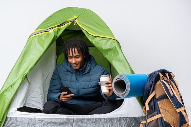 Junger afroamerikanermann in einem grünen zelt des campings, das kaffee hält, um und ein handy wegzunehmen