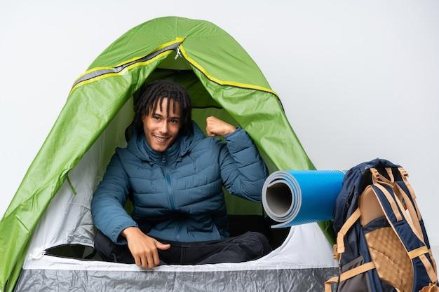 Junger afroamerikanermann in einem grünen zelt des campings, das starke geste tut