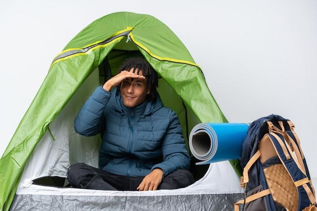 Junger afroamerikanermann in einem grünen zelt des campings, das weit weg mit hand schaut, um etwas zu schauen