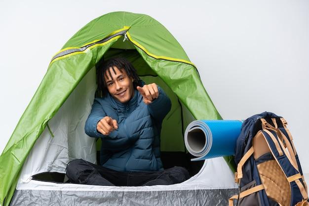Junger afroamerikanermann in einem grünen zelt des campings zeigt finger auf sie beim lächeln