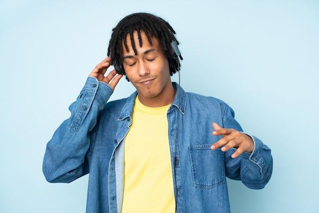 Junger afroamerikanermann lokalisiert auf blauer wand, die musik und tanz hört