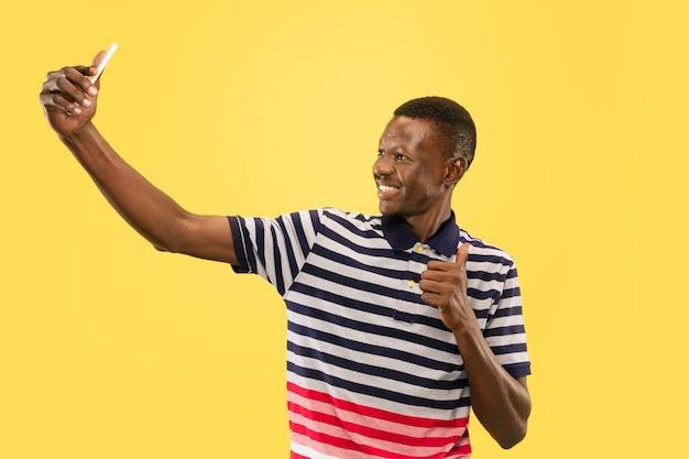 Junger afroamerikanermann lokalisiert auf gelbem studiohintergrund, menschliches gefühlskonzept