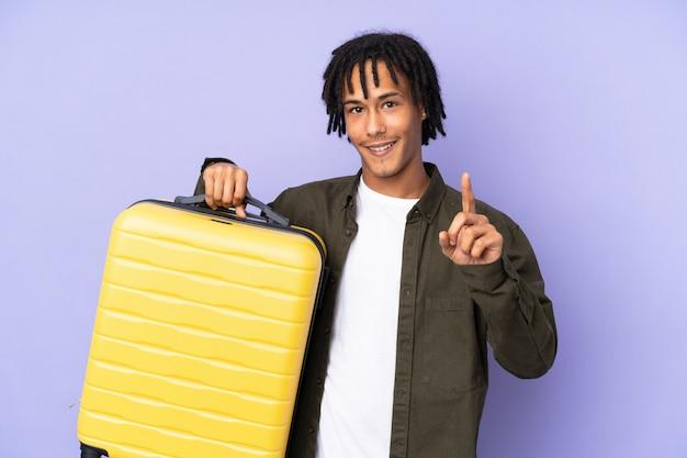 Junger afroamerikanermann lokalisiert auf lila hintergrund im urlaub mit reisekoffer und zählen eines