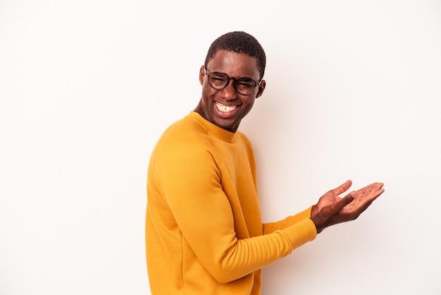 Junger afroamerikanermann lokalisiert auf weißem hintergrund, der einen kopienraum auf einer palme hält.