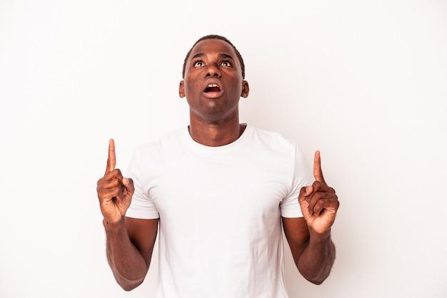 Junger afroamerikanermann lokalisiert auf weißem hintergrund, der oben mit geöffnetem mund zeigt.