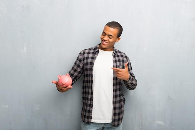 Junger afroamerikanermann mit dem karierten hemd, das ein großes piggybank hält