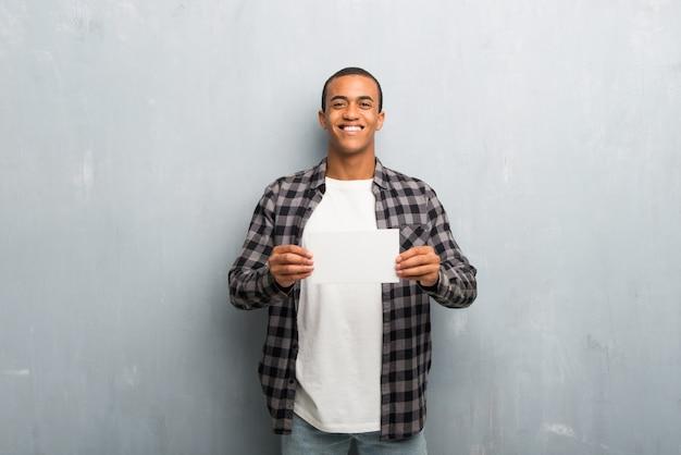 Junger afroamerikanermann mit dem karierten hemd, das ein leeres weißes plakat für einfügen ein konzept hält