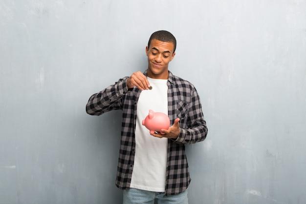 Junger afroamerikanermann mit dem karierten hemd, das ein sparschwein nimmt und glücklich ist, weil es voll ist