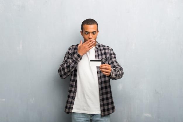 Junger afroamerikanermann mit dem karierten hemd, das eine kreditkarte und überrascht hält
