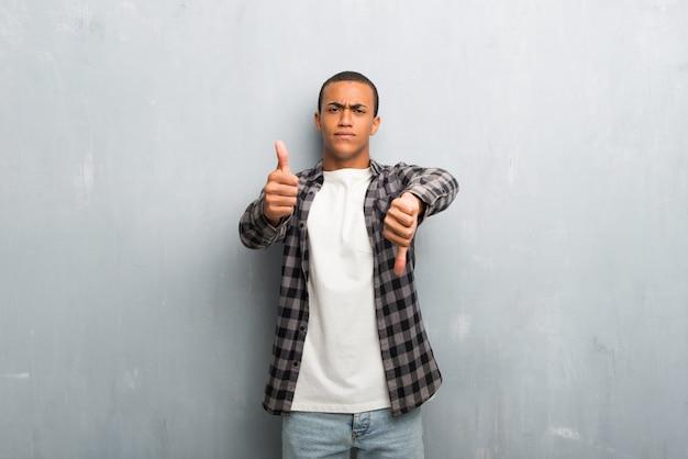 Junger afroamerikanermann mit dem karierten hemd, das gut-schlechtes zeichen macht