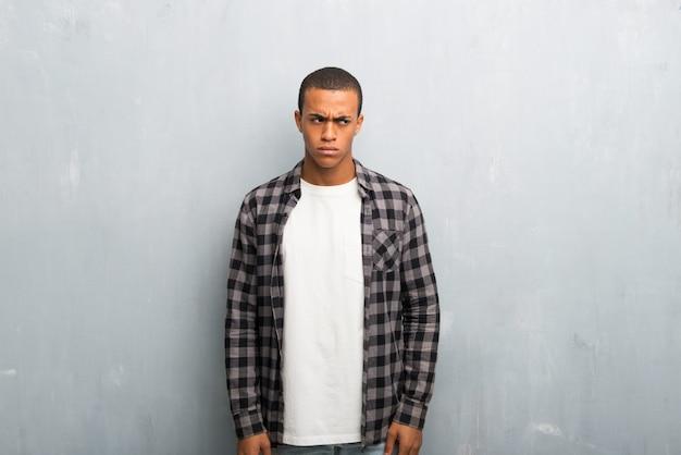 Junger afroamerikanermann mit dem karierten hemdgefühl gestört