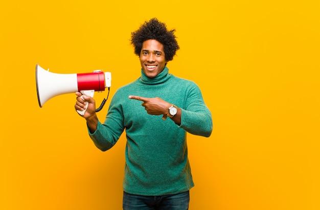 Junger afroamerikanermann mit einem megaphon auf orange backg