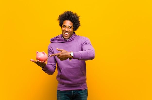 Junger afroamerikanermann mit einem sparschwein gegen orangenrückseite