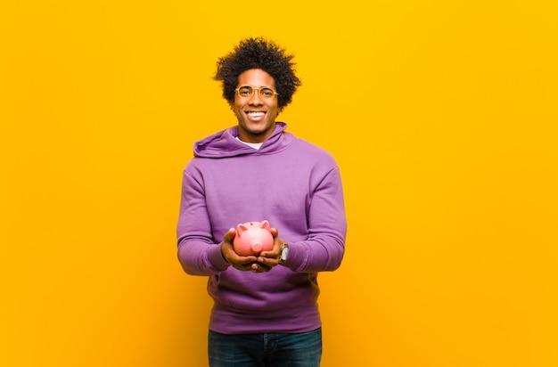 Junger afroamerikanermann mit einem sparschwein