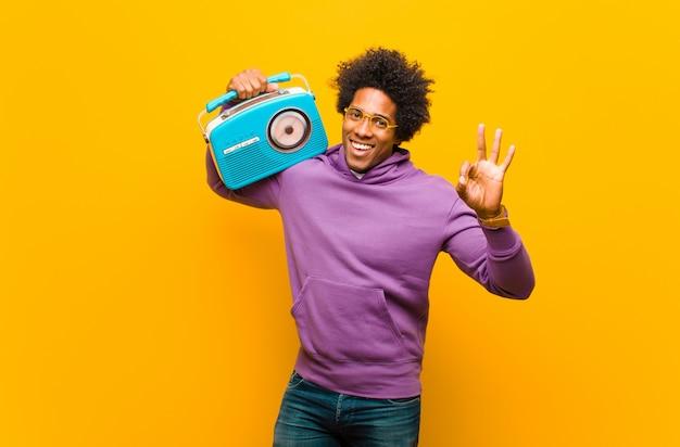 Junger afroamerikanermann mit einem weinleseradio gegen orange b