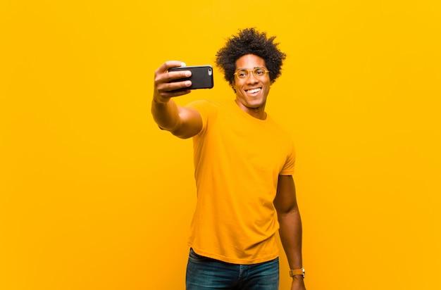 Junger afroamerikanermann mit einer intelligenten telefonorange