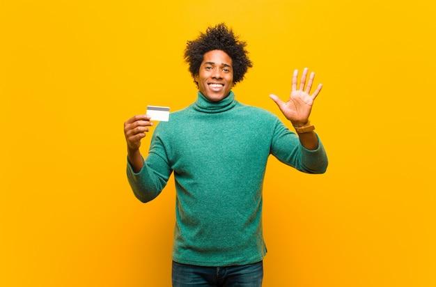Junger afroamerikanermann mit einer kreditkarteorange