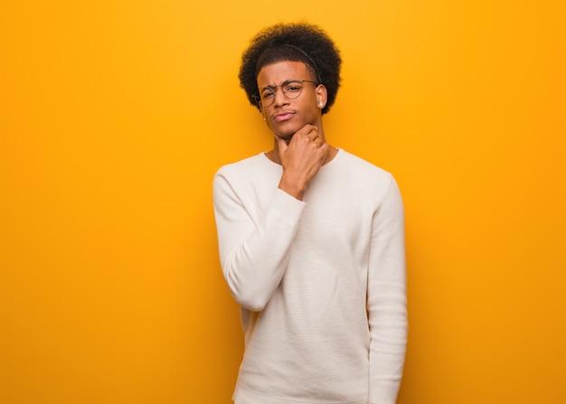 Junger afroamerikanermann über einem orange wandhusten, einem kranken wegen eines virus oder einer infektion