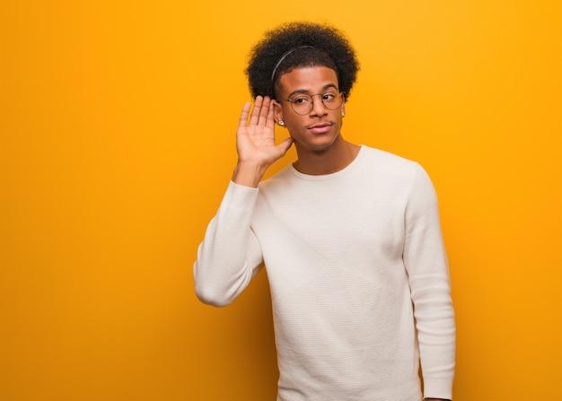 Junger afroamerikanermann über einem orange wandversuch zum hören eines klatsches