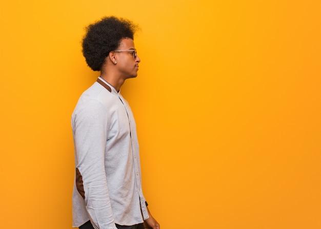 Junger afroamerikanermann über einer orange wand auf der seite, die nach vorne schaut