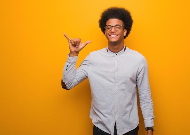Junger afroamerikanermann über einer orange wand, die eine felsengeste tut