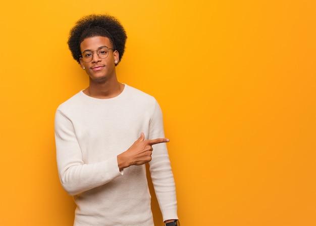 Junger afroamerikanermann über einer orange wand lächelnd und auf die seite zeigend