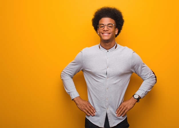 Junger afroamerikanermann über einer orange wand mit den händen auf hüften