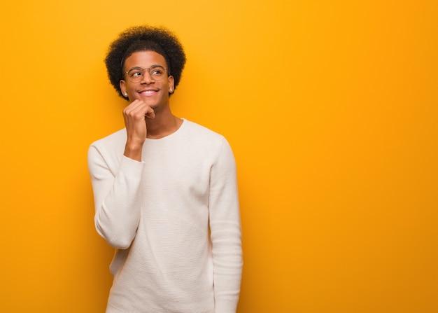 Junger afroamerikanermann über einer orange wand zweifelnd und verwirrt