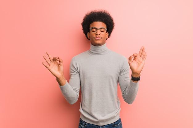 Junger afroamerikanermann über einer rosa wand, die yoga durchführt