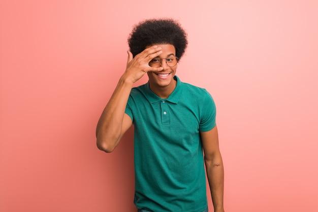 Junger afroamerikanermann über einer rosa wand gleichzeitig verlegen und lachend