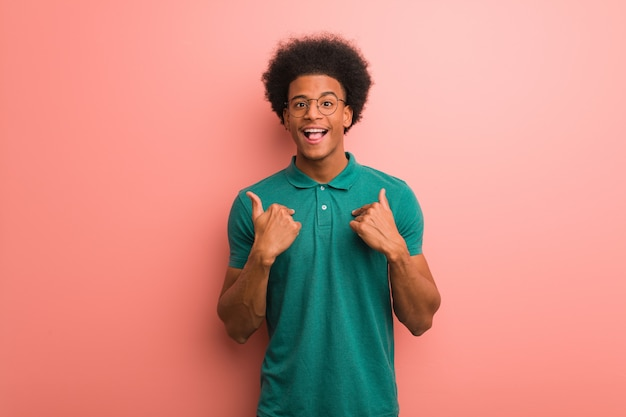 Junger afroamerikanermann über einer rosa wand überrascht, fühlt sich erfolgreich und wohlhabend