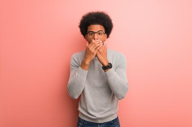 Junger afroamerikanermann über einer rosa wand überrascht und entsetzt