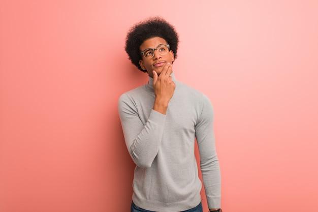 Junger afroamerikanermann über einer rosa wand zweifelnd und verwirrt