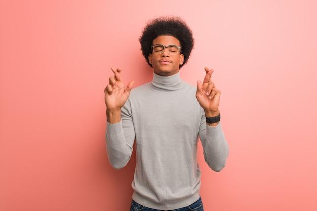 Junger afroamerikanermann über fingern einer rosa wandüberfahrt für das haben des glücks