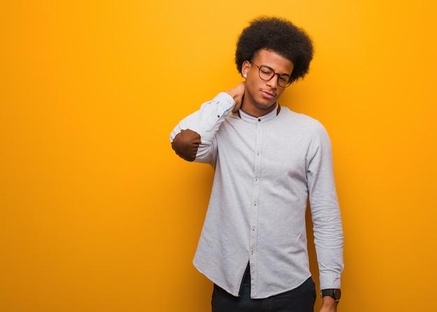 Junger afroamerikanermann über leidenden nackenschmerzen einer orange wand