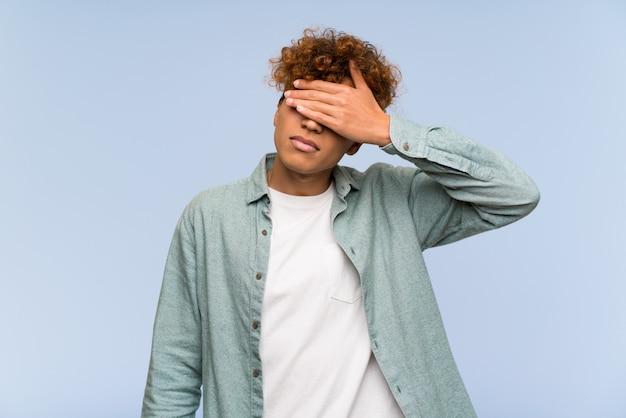 Junger afroamerikanermann über lokalisierten blauen wandverkleidungsaugen durch hände. ich will nichts sehen